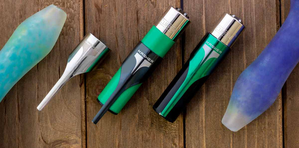 Kasher Lighter Tools made for Clipper Lighters against a wooden background. Kashers displayed left to right include a silver Kasher with no lighter, a black Kasher partially slid down a green Clipper lighter, and a green Kasher adorning a black lighter in the fully retracted resting position.
