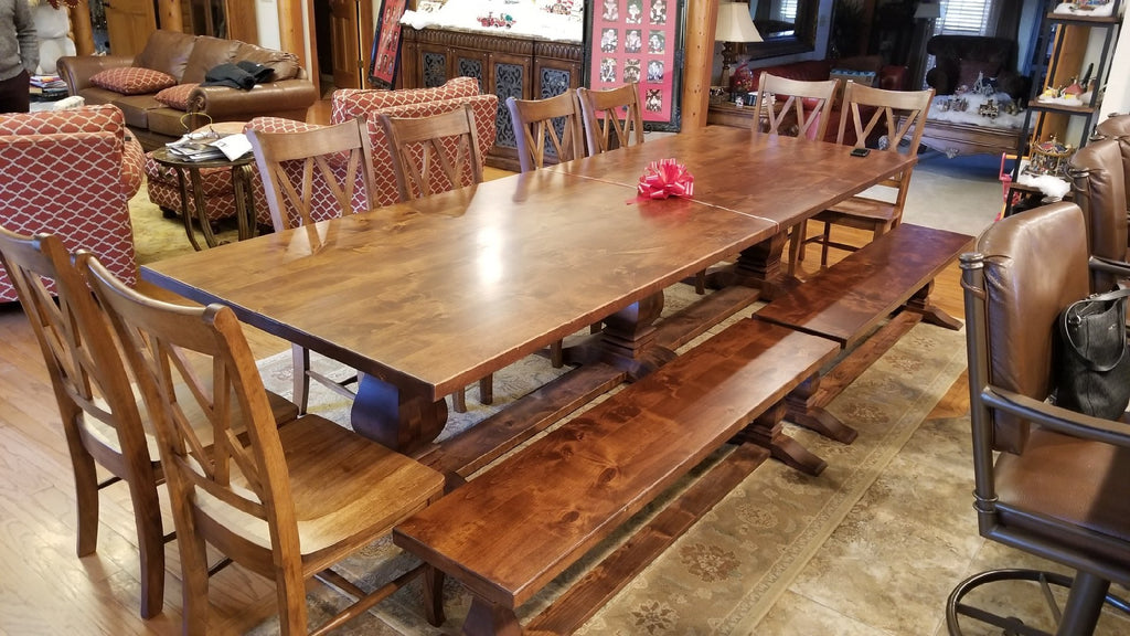 Two 5.5'  Heirloom Pedestal Benches in Tuscany Finish with Top Knots Filled. Also pictured a 11' Heirloom Pedestal Table in Tuscany Finish with Top Knots Filled and our Double X-Back Wood Dining Chair in Tuscany Finish.
