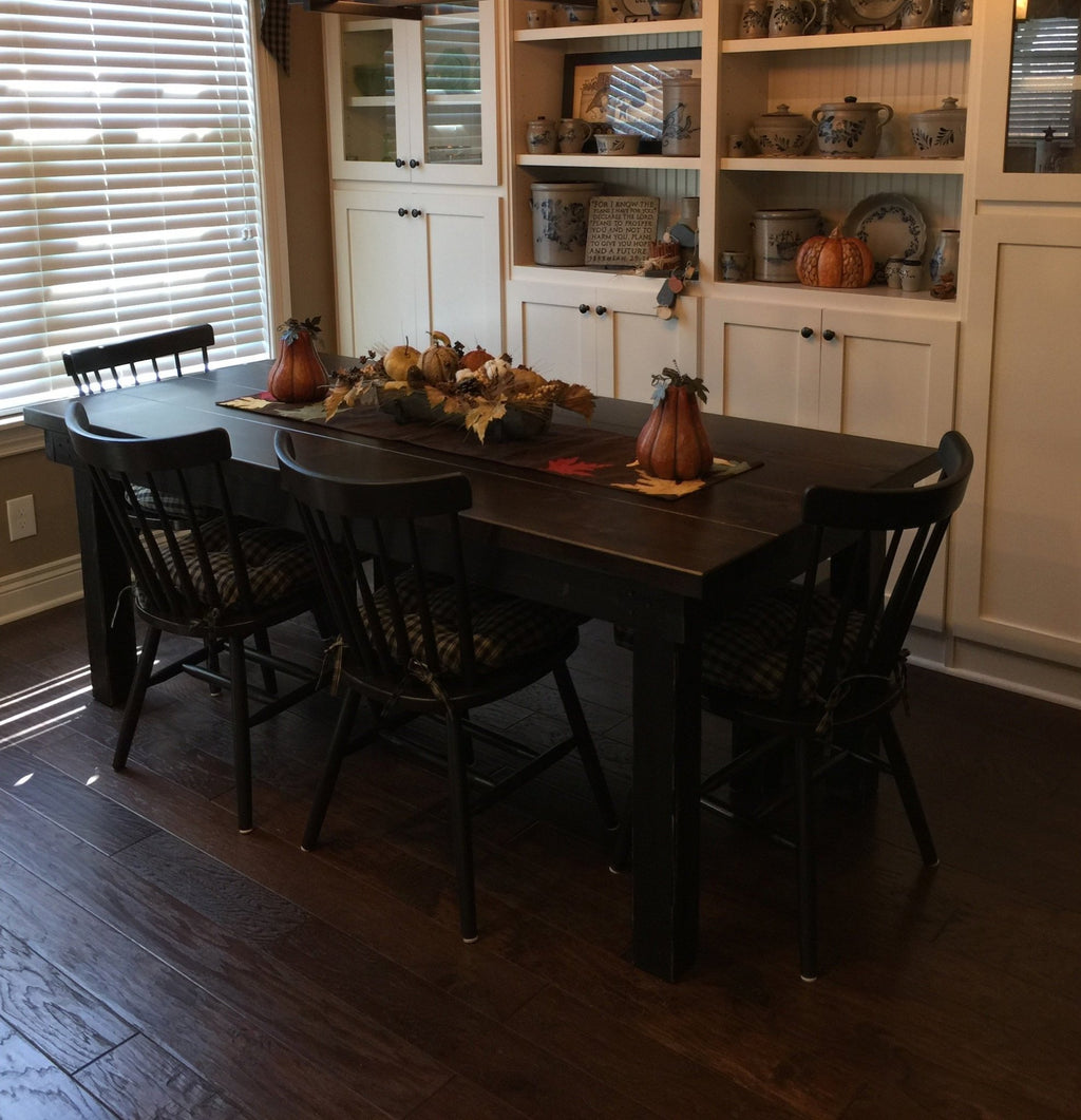 "6.5' L x 37"" W Farmhouse Table with a Boarded Look - Grooved and Filled Top Knots in Tobacco Finish and a Painted Black Distressed base. Also pictured our Rustic Windsor Dining Chair Painted Black with Tobacco Finish on the seats."