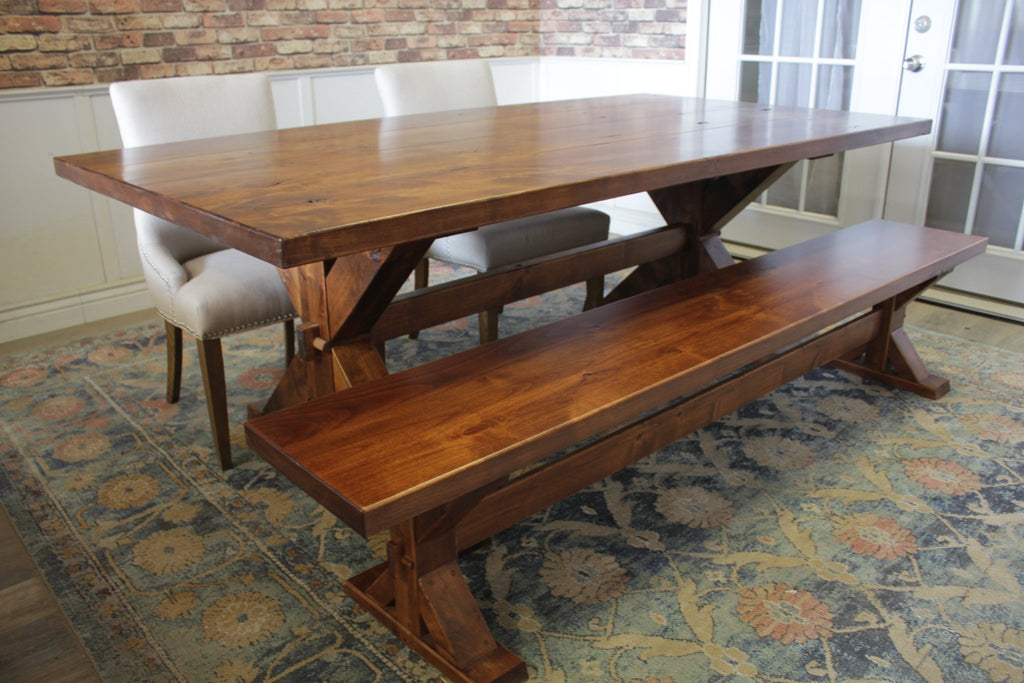 "7'L X 44""W X 30""T Trestle Table in Tuscany Finish with Boarded Look - Grooved Top Style and natural open knots. Also pictured a 7' Trestle Bench in Tuscany and two Ashford Linen Dining Chairs."