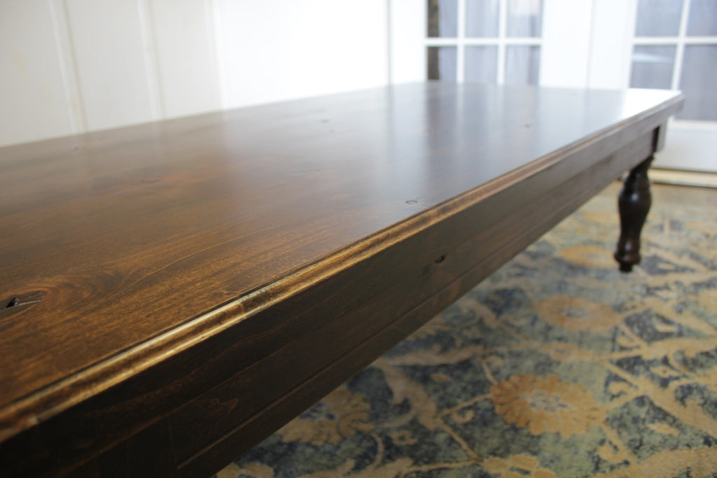 "60"" L X 30"" W X 18"" T Abigail Turneg Leg Coffee Table in Tobacco Finish with natural open knots"