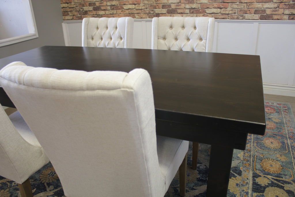 Farmhouse Table - Hardwood in Charred Ember Finish with Jointed Top and Charred Ember Finish base. Also pictured Lauren Tufted Linen Chair in Off White Linen