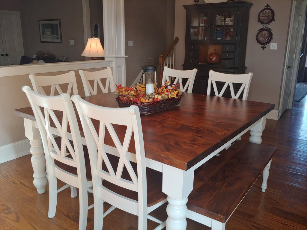 "66"" Square Baluster Table Knotty Alder hardwood top in Tuscany finish and ivory painted base. Jointed with Filled top Knots. Pictured with our Dianne Bench upgraded to Knotty Alder top in Tuscany finish with Ivory painted base and Double X-Back Dining Chair."