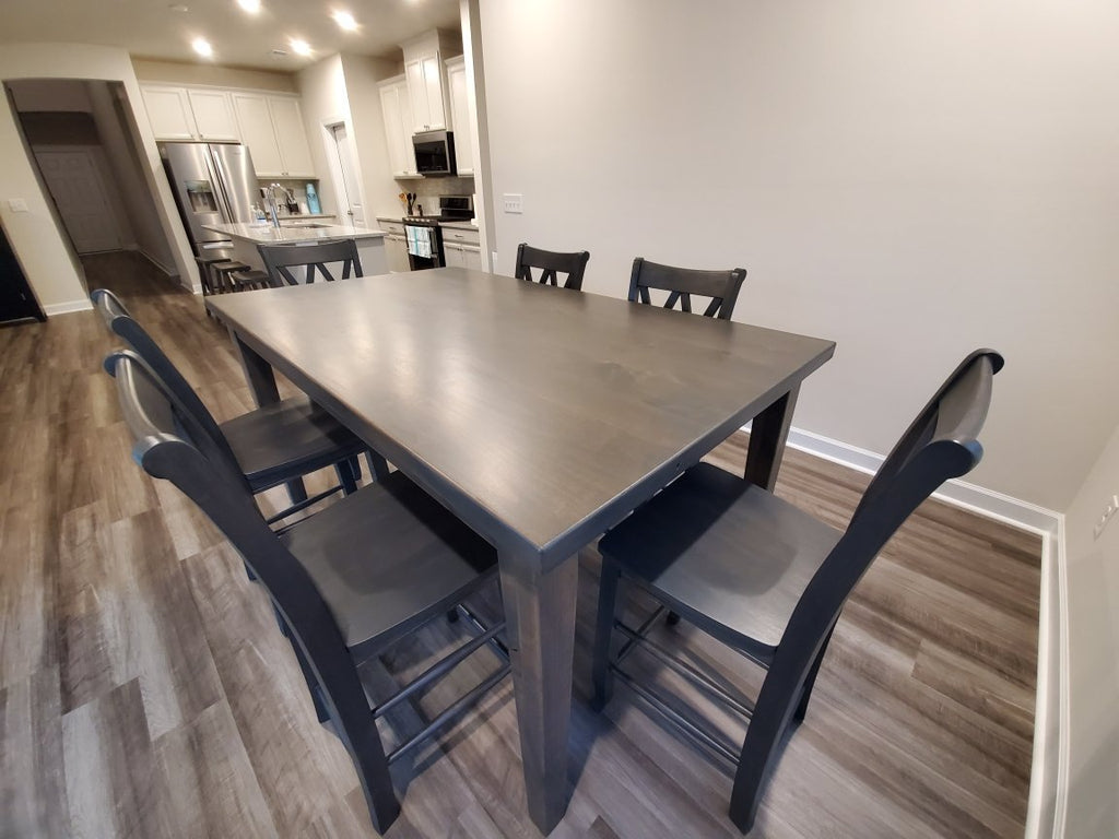"Double X-Back Stools in Deep Grey Finish.  Also pictured a 6' L X 42"" W X 36"" T Ava Parsons Table in Deep Grey Finish with Filled Top Knots at Counter Height and three Saddle Stools in Deep Grey Finish."