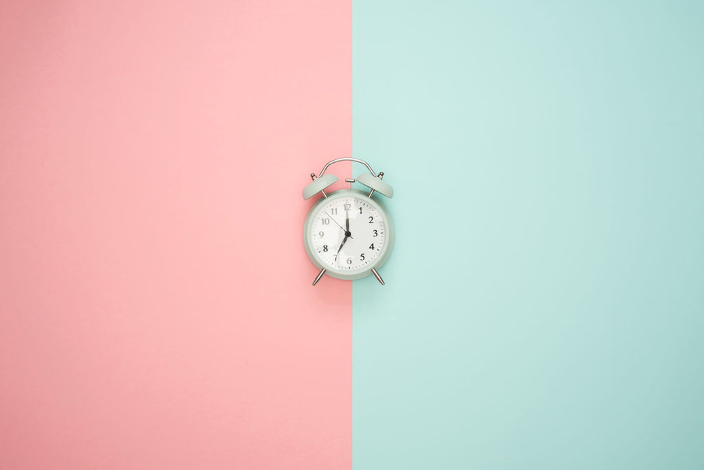 alarm clock in the middle of a pink and green background