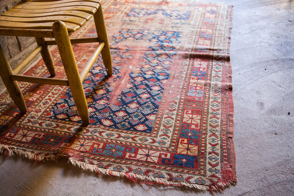 Worn antique Caucasian rug