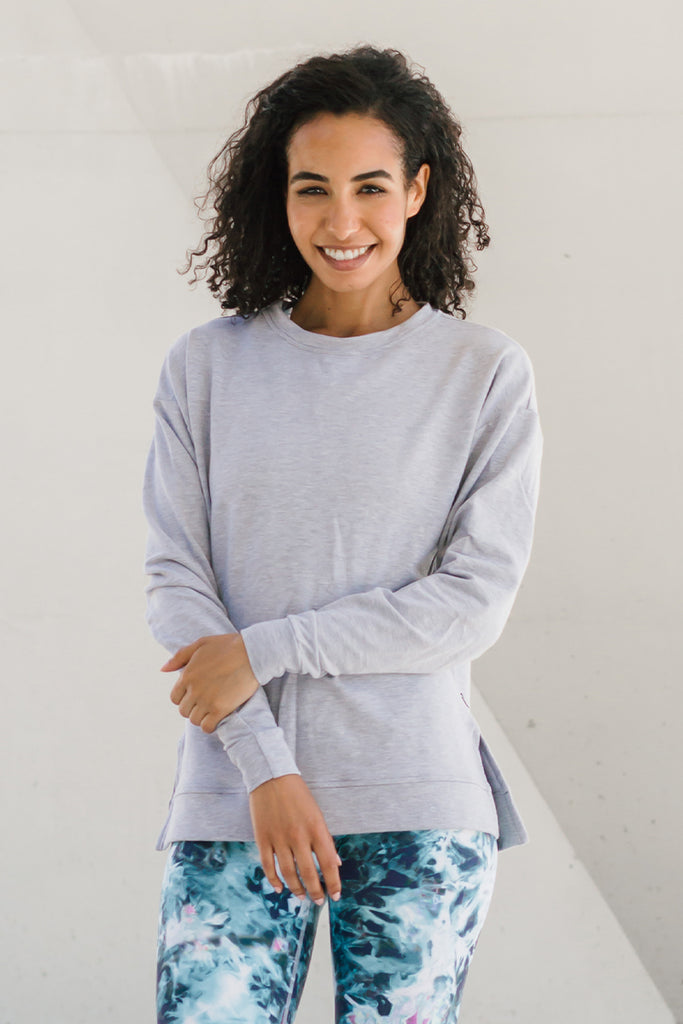 Woman wearing light grey crewneck sweater ethically-made in Canada.