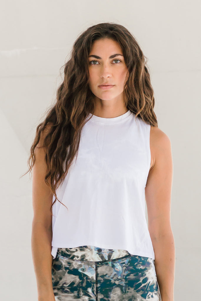 Woman with long dark hair wearing white cropped muscle tank top, ethically-made in Canada.