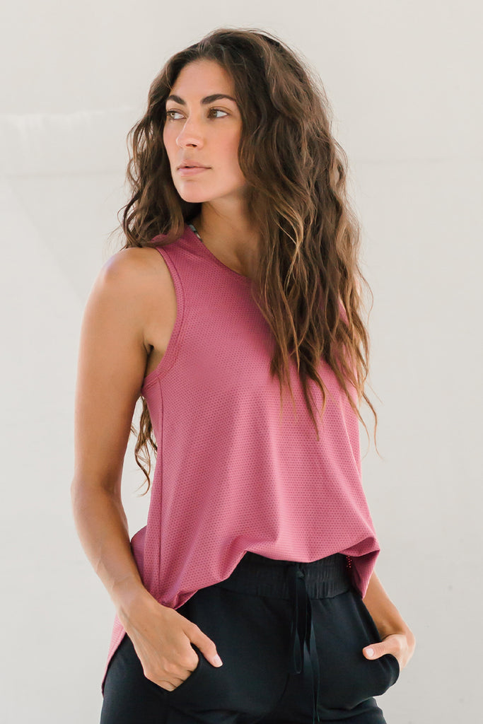Woman wearing pink tank top with racerback and high neckline tucked into black joggers.