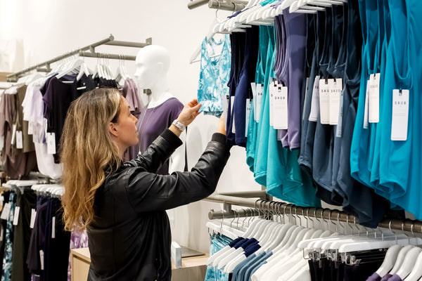 A woman shops the clothing rack looking at sports bras, tank tops and leggings at DAUB on Granville.