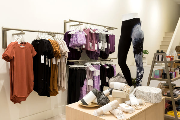 A photo of the interior of DAUB on Granville showing our tee-shirt dress, sports bras and leggings on display.