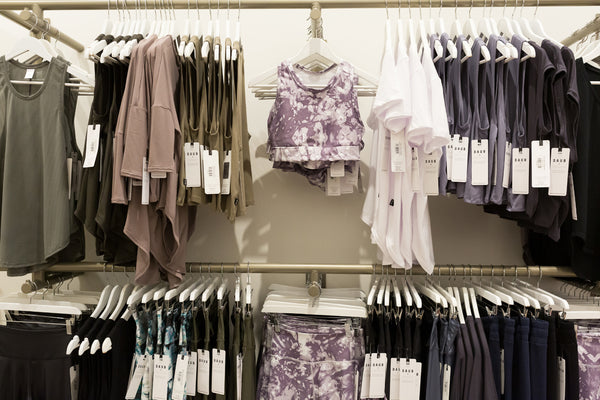 A photo of a clothing display at 3012 Granville Street with sports bras, tank tops, sweaters, leggings and activewear.