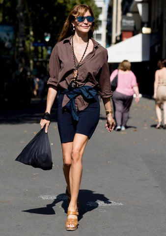 Bike shorts paired with Sandals and a Brown Blouse.
