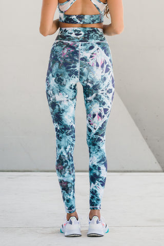 Woman standing wearing blue and white tie-dye yoga pants.