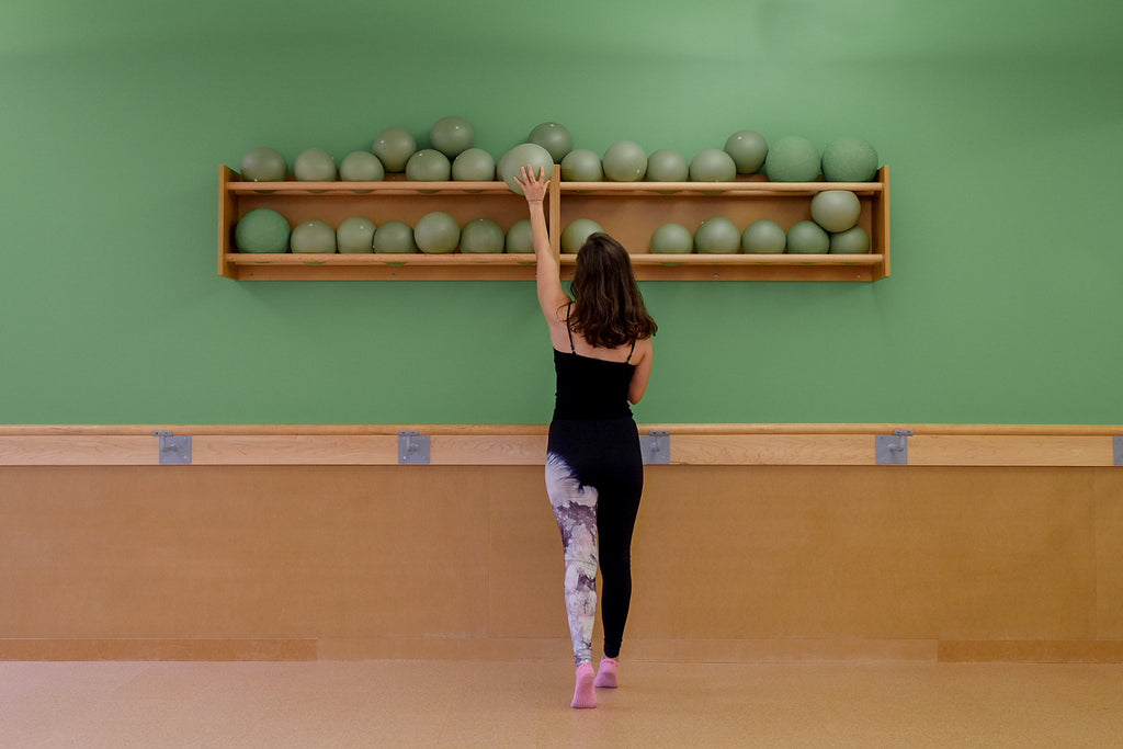 A brunette woman is in a barre studio placing a green ball on a shelf