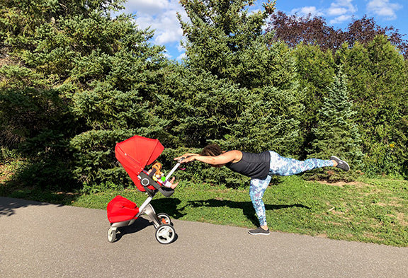 A woman works on glute exercises in the park and uses her stroller to balance.