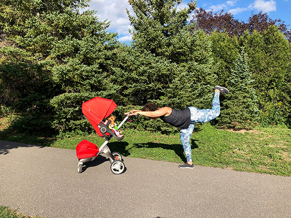 A woman uses her stroller to do a booty workout in the park.