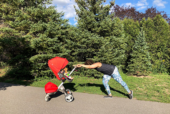 A woman leans parallel to the ground holding onto her stroller getting ready for a workout.