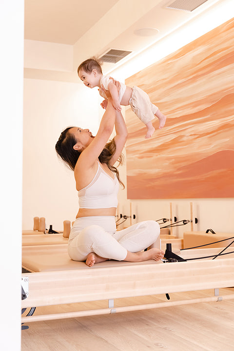 Vancouver Yogi Cam Lee holds her baby up in the air for post-natal pilates at Core Community