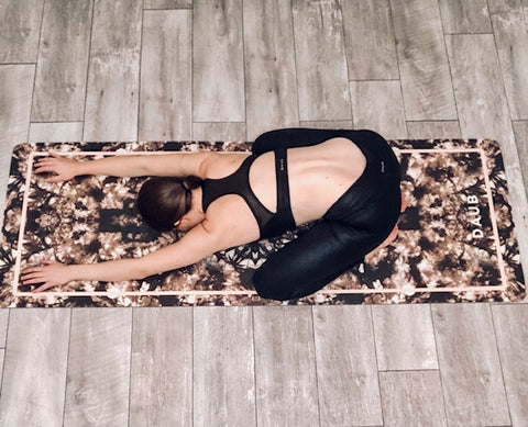 A woman is seen stretching while seated on a brown tie dye yoga mat