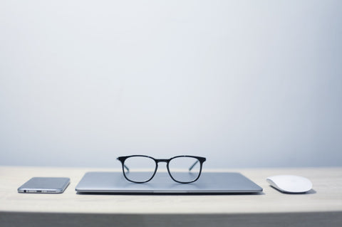 Glasses on a laptop with a mouse. Office with a white desk and grey wall.