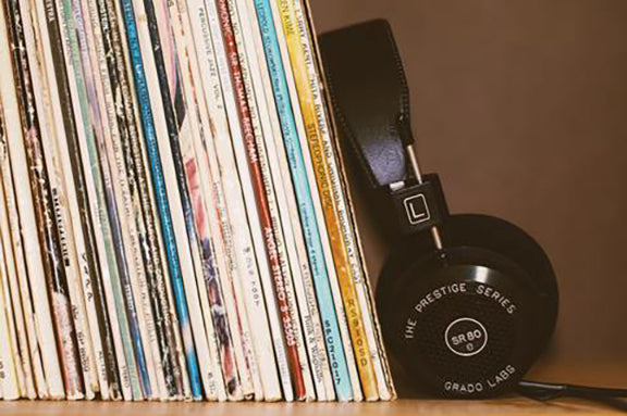 A stack of records sits on a bookshelf with black headphones