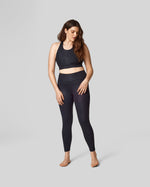 A size 12 model wears a size L in the black cheetah print long-line sports bra and high waisted legging.