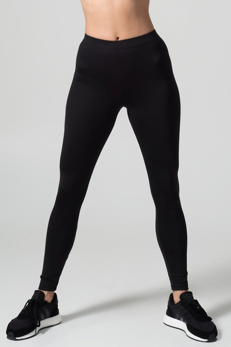A woman's legs are shown wearing black leggings.