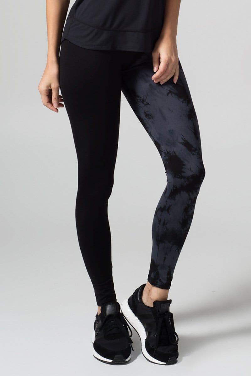 A woman with blonde hair models a black tank top and leggings. The right pant leg of the leggings is black, while the other is tie-dyed  in charcoal grey and black.