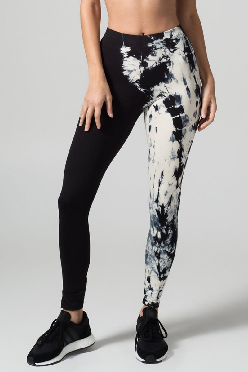 A woman with blonde hair models a black sports bra and leggings. The right pant leg of the leggings is black, while the other is tie-dyed  in cream and black.