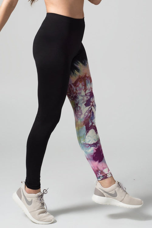 A woman with red hair models a black sports bra and leggings. The right pant leg of the leggings is black, while the other is tie-dyed bright and purple colours.
