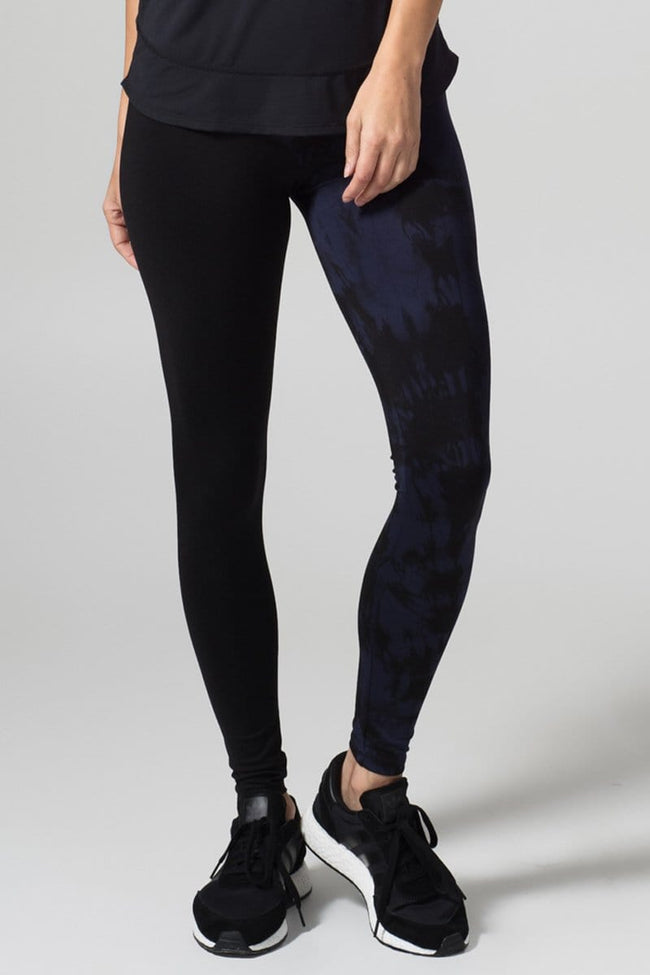 A woman with blonde hair models a black tank top and leggings. The right pant leg of the leggings is black, while the other is tie-dyed in navy and black.