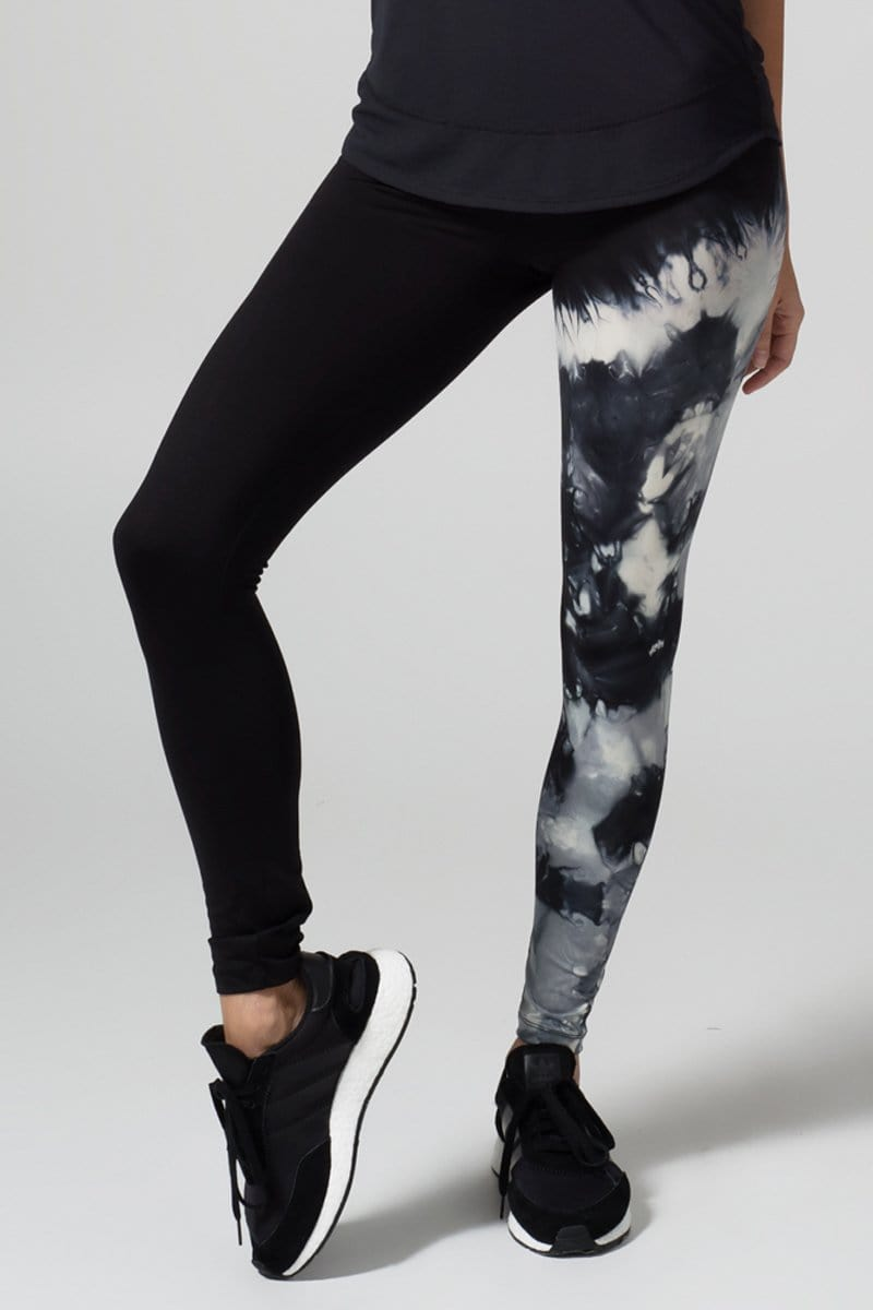 A woman with blonde hair models a black tank top and leggings. The right pant leg of the leggings is black, while the other is tie-dyed grey tones.