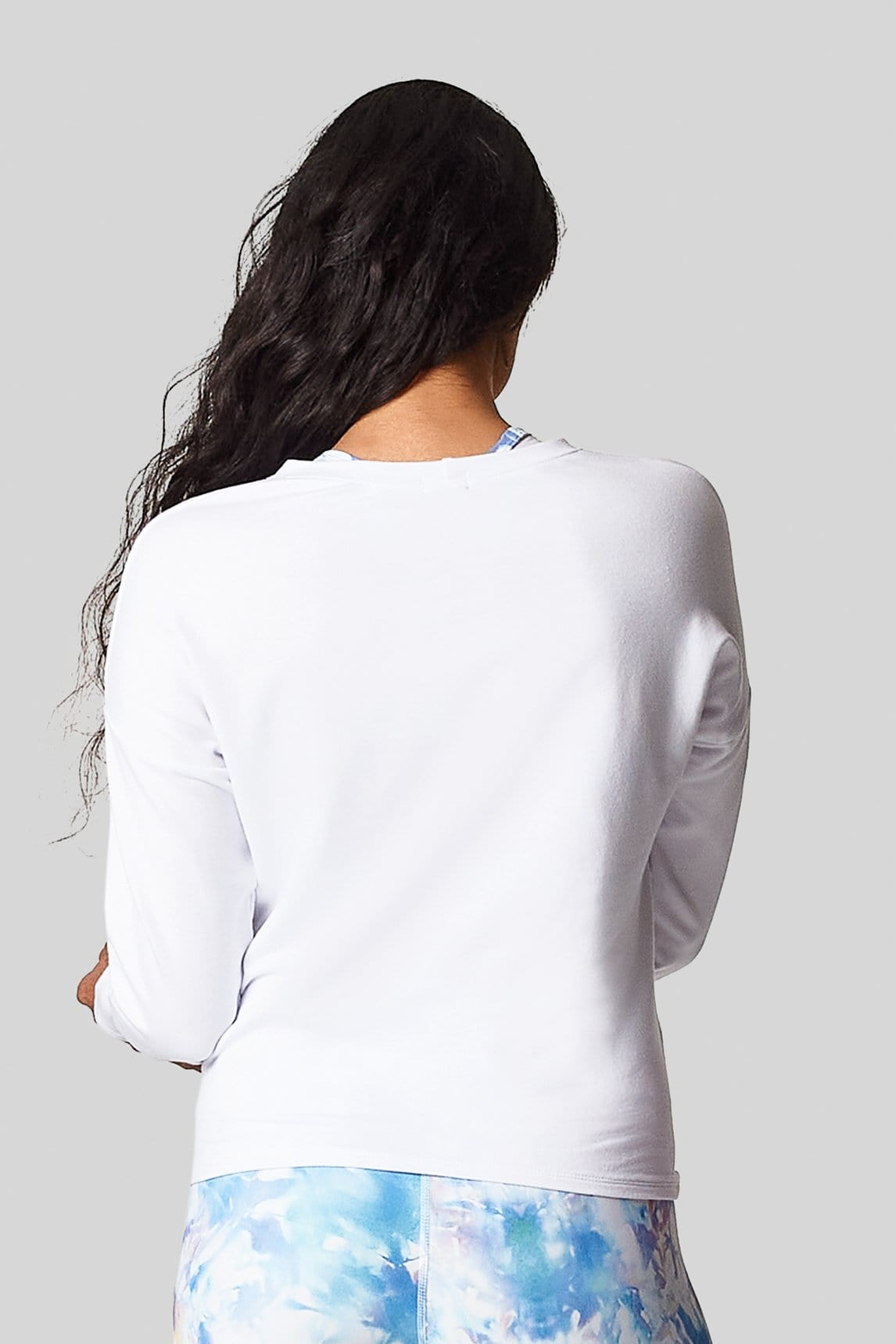 A back view of a woman wearing a white, hip length french terry sweatshirt.