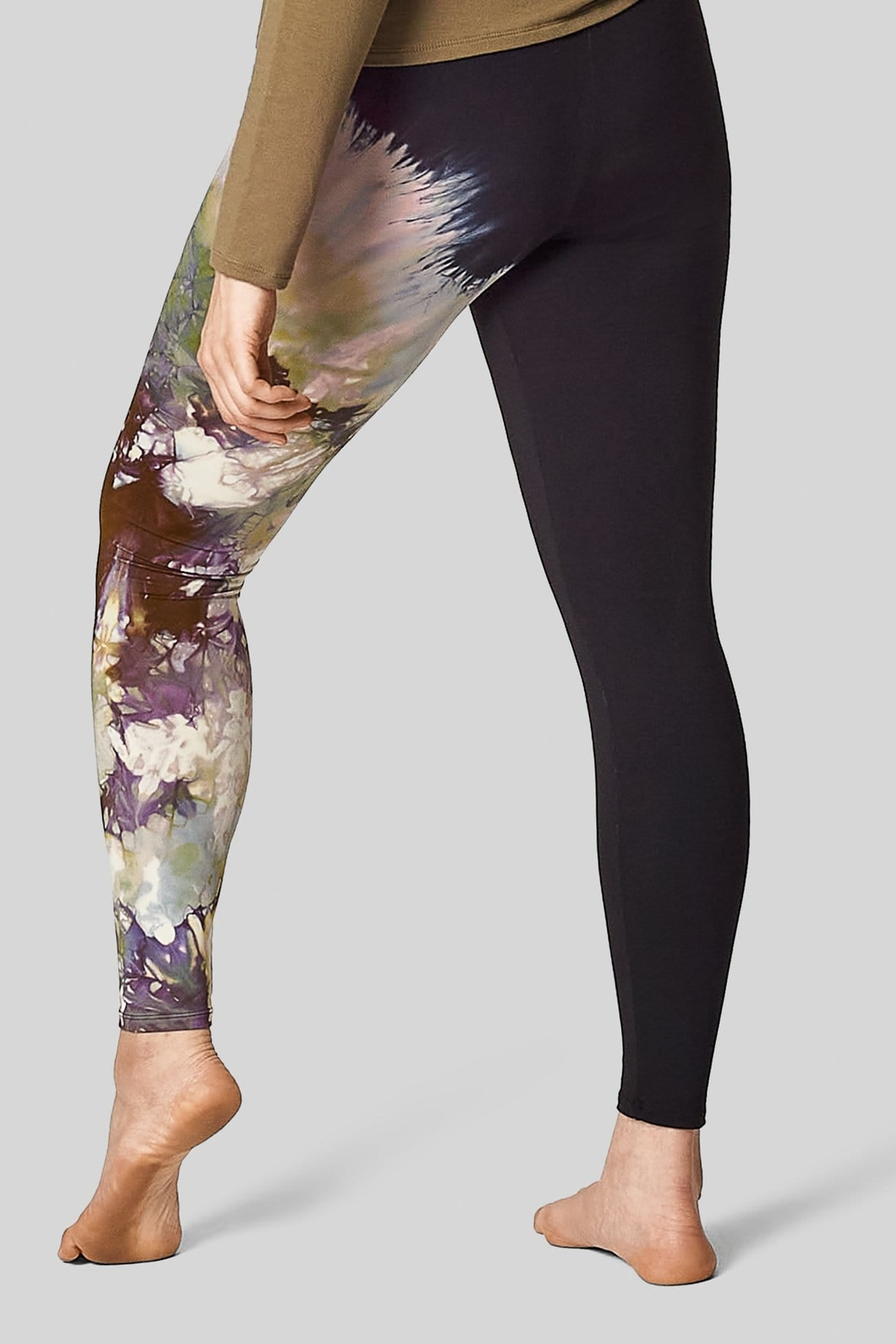 A back view of a woman wearing tie-dyed leggings, made in Canada.