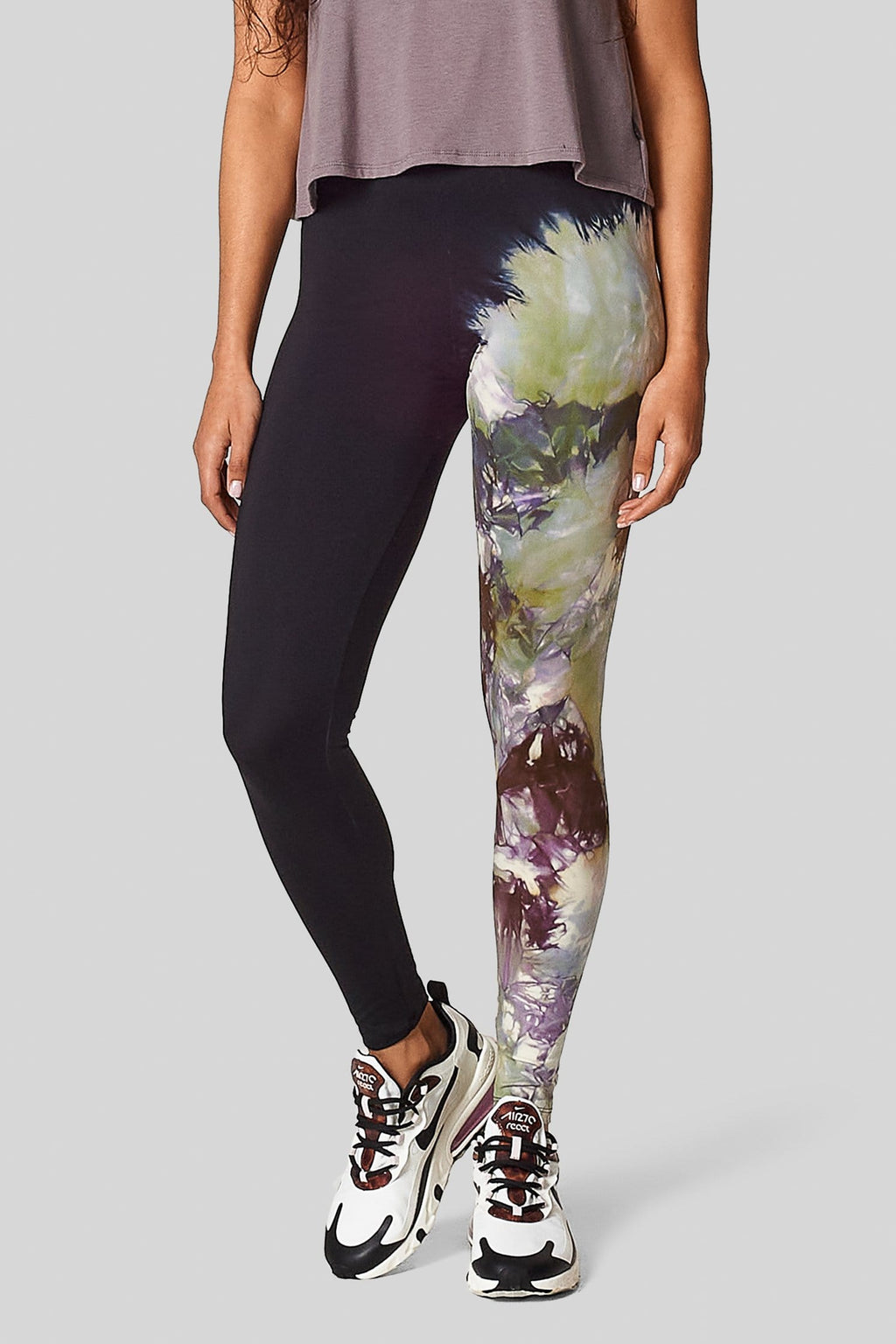 A woman wears a pair of leggings with one leg dyed black and one leg tie-dye