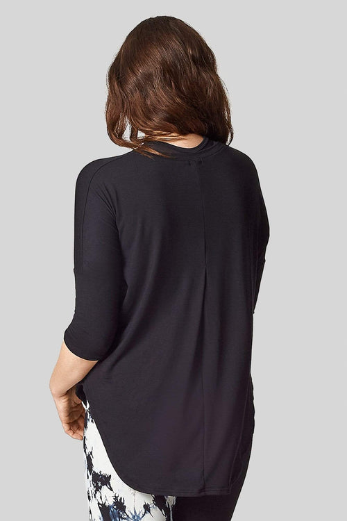 A brunette is wearing a 3/4 length sleeve tee shirt with a pleat in the back starting at the bust.