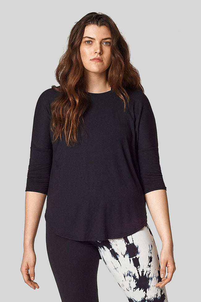 A model wears a t-shirt with 3/4 length sleeves in black with a hi-lo hem (longer in the back).