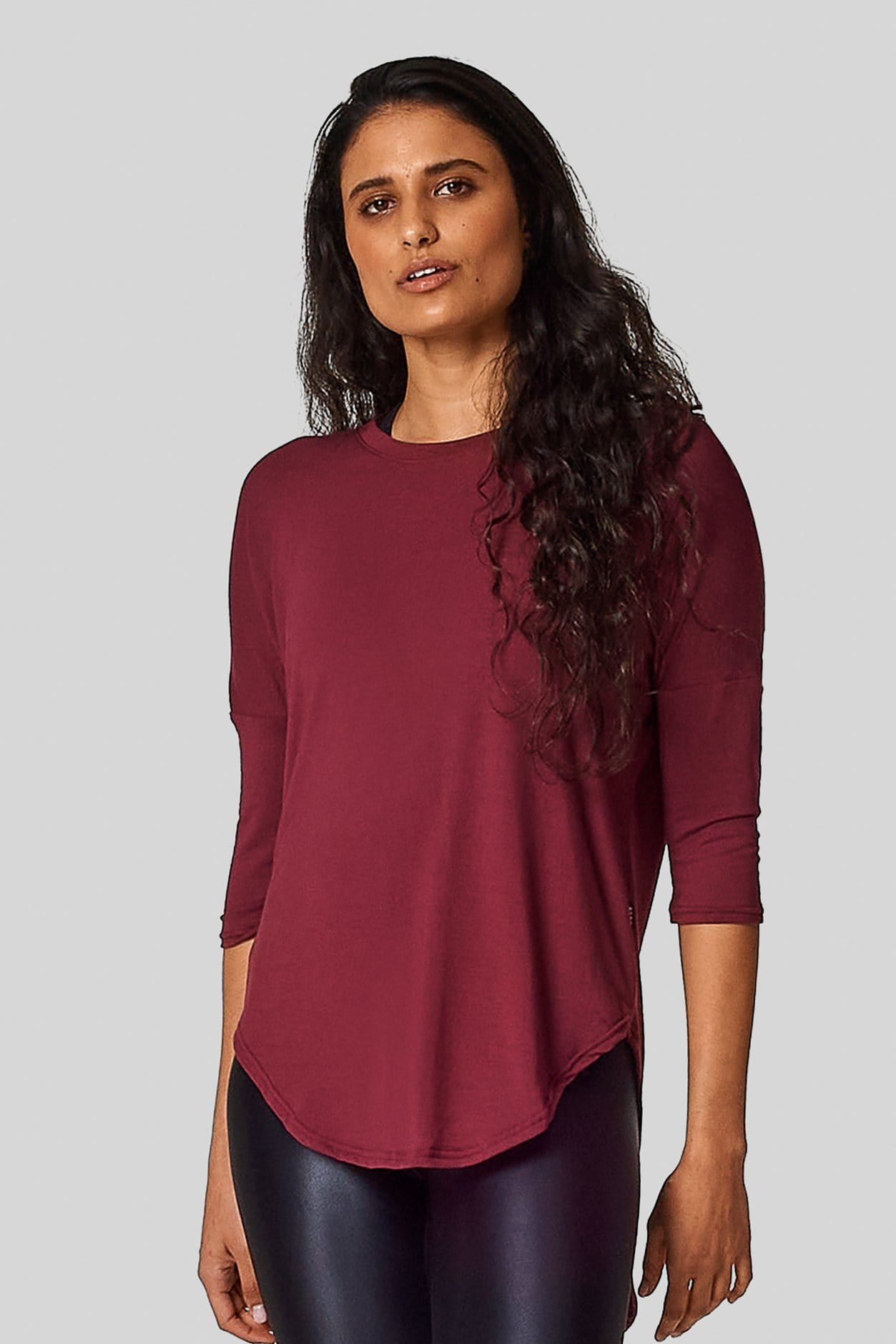 A girl wears a red tee shirt with a scooped hem & 3/4 length sleeves