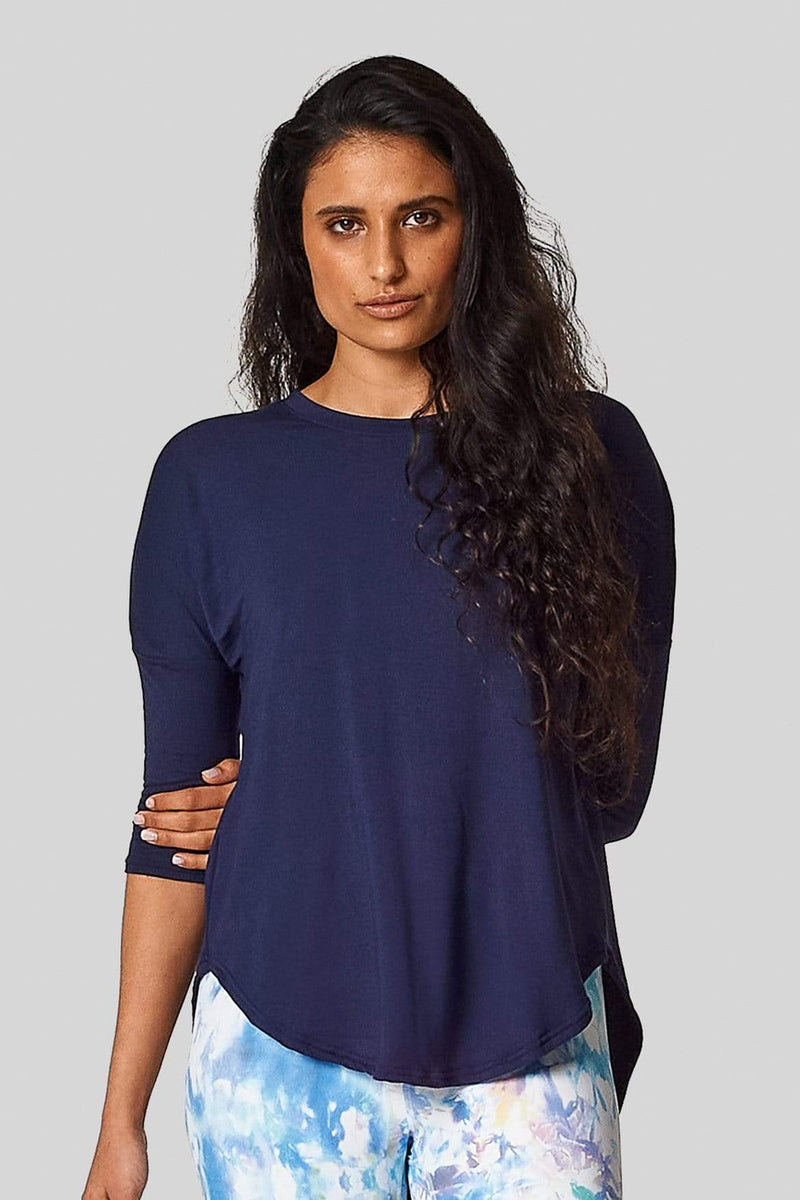 A woman wears a navy teeshirt with 3/4 length sleeves and printed leggings.