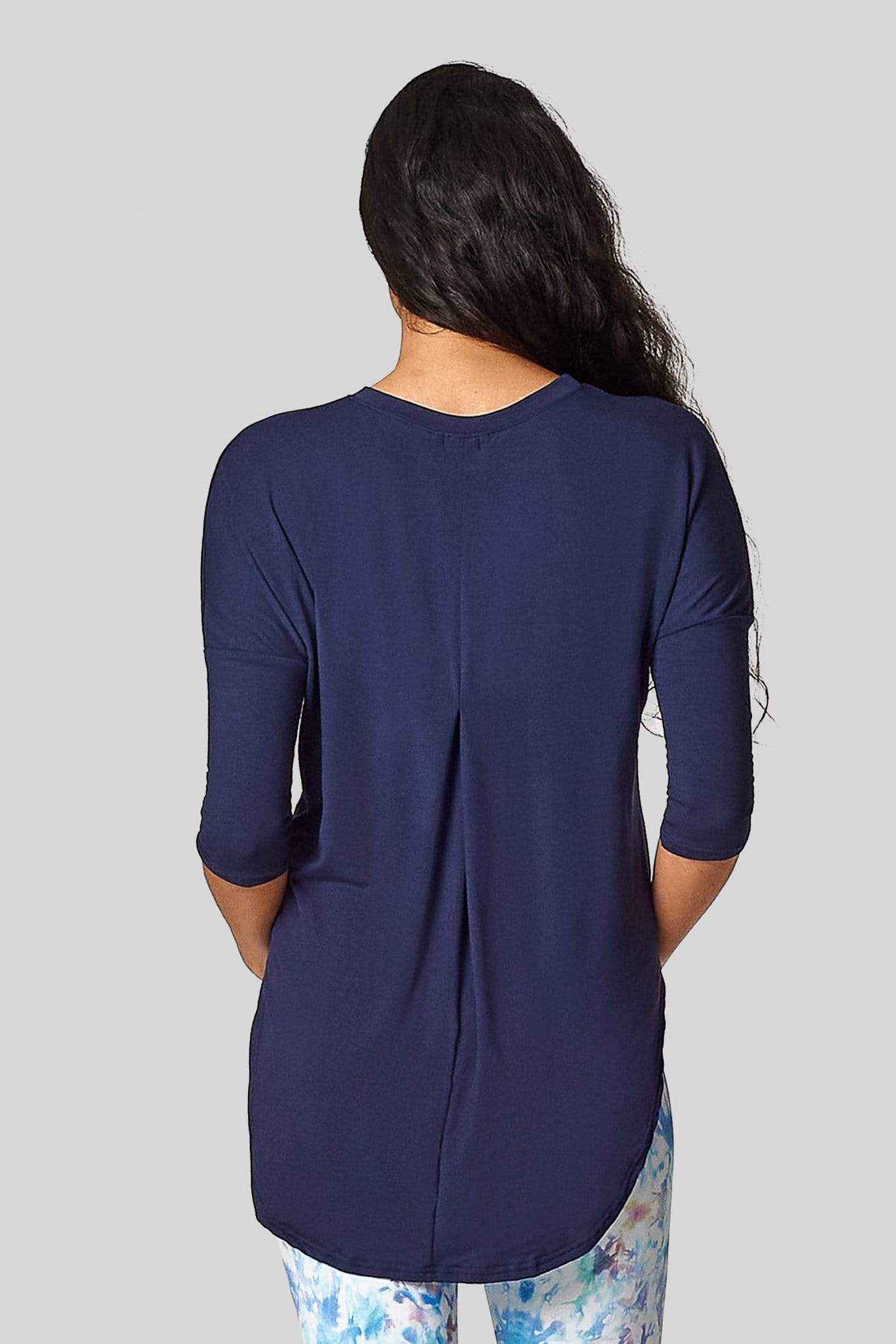 A woman's back faces the camera and she wears a blue 3/4 length tee shirt with a pleat in the back.