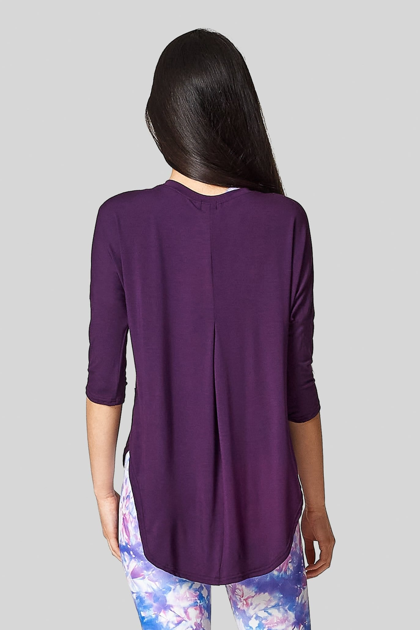 A woman wears a plum t-shirt with a long hem & pleat at the back.