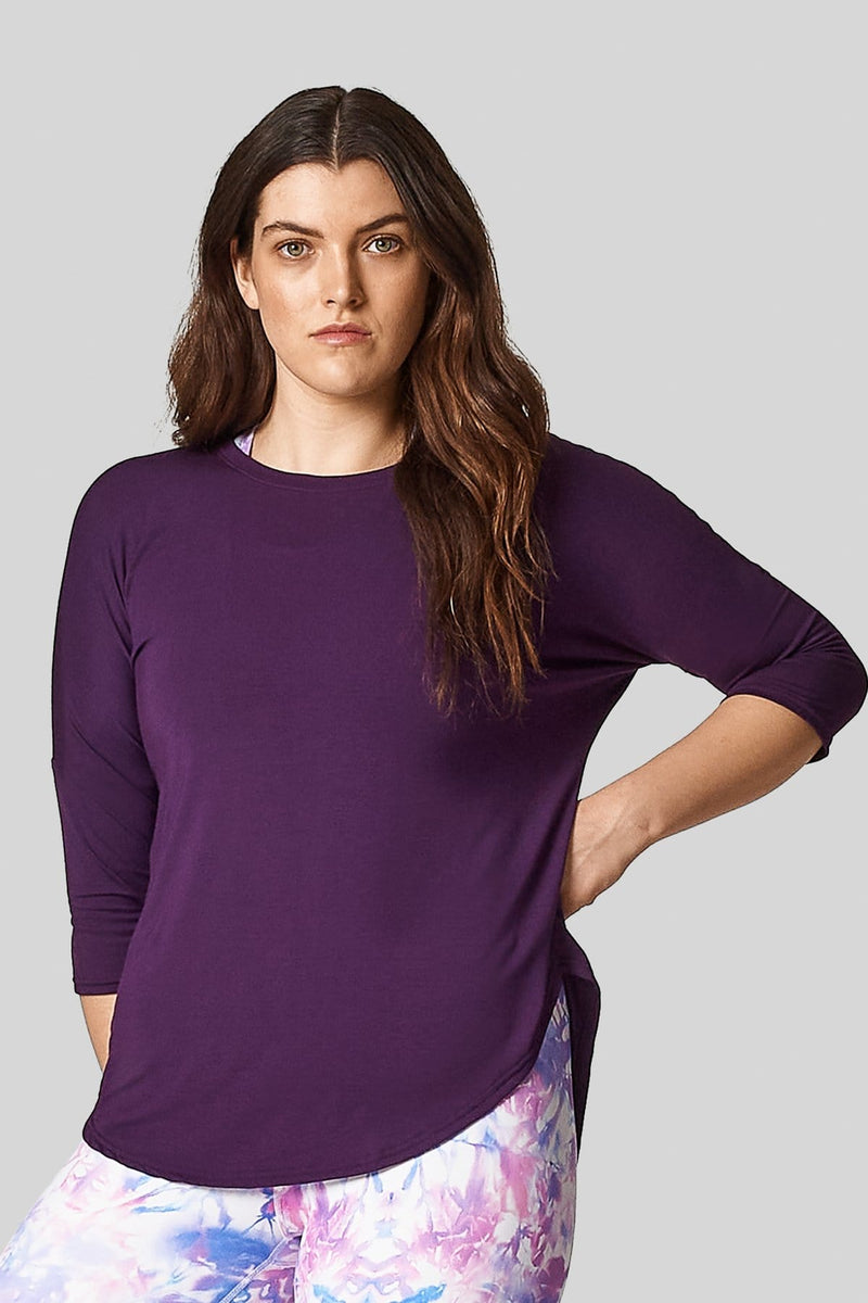 A young woman is modelling a violet shirt with 3/4 length sleeves and printed leggings.