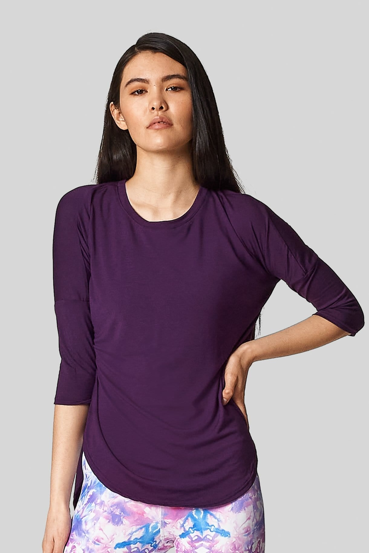 An asian female is wearing a purple t-shirt with 3/4 length sleeves.
