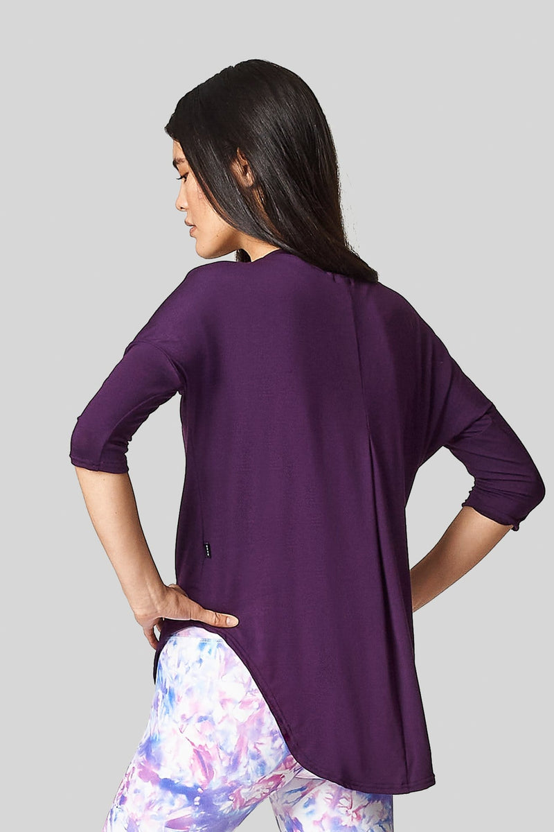 A black haired female is wearing a purple tee-shirt with a scooped hem that is long in the back to cover her bum.