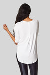 The back view of the Ainsley Tee with a back box pleat and low hem for bum coverage.