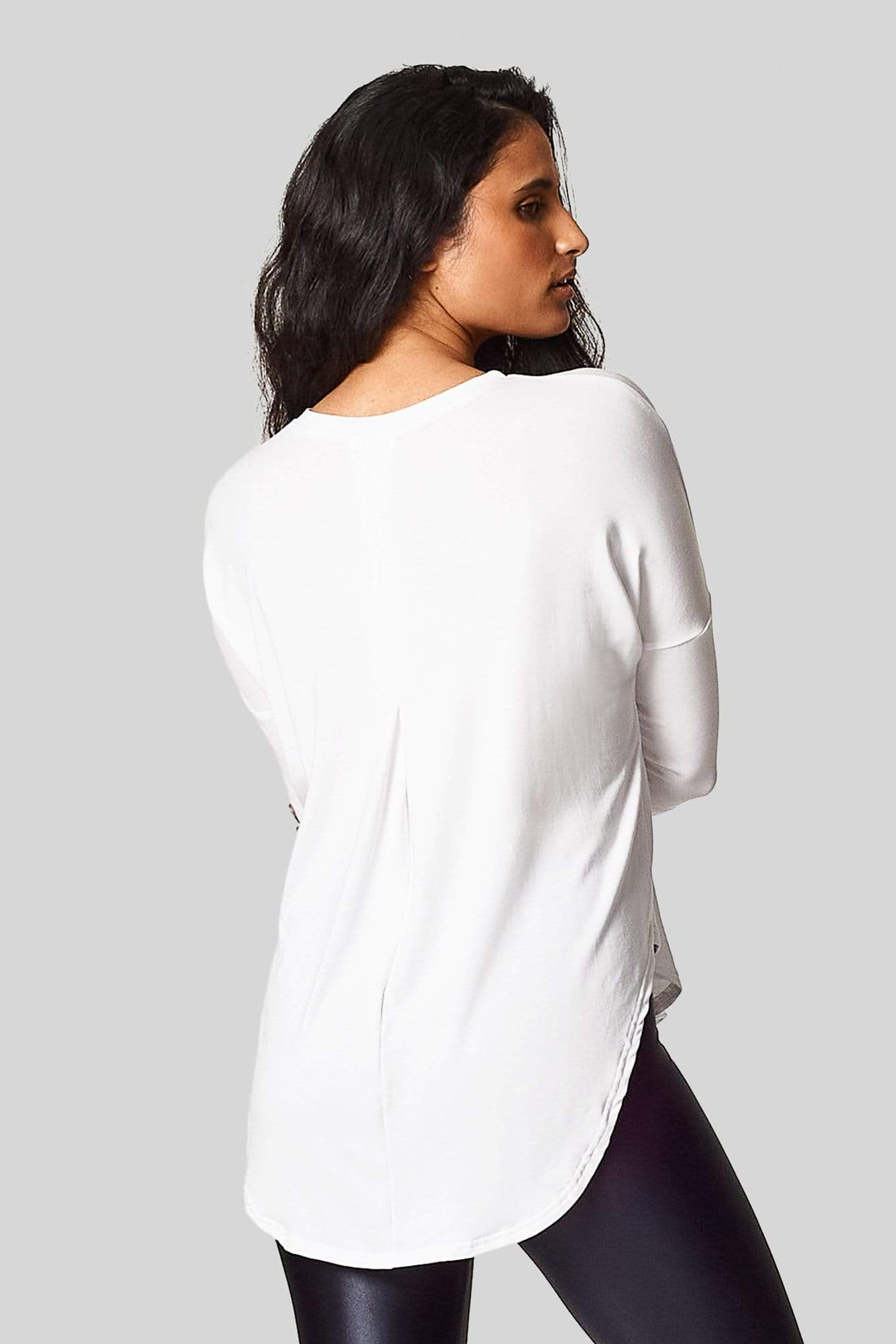 A brunette shows us the back pleat in her white 3/4 length sleeve tee-shirt.