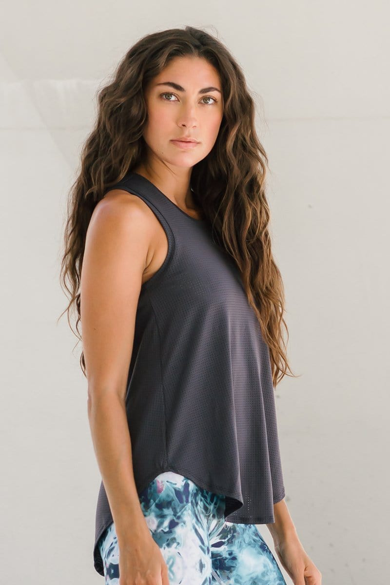 A brunette model wears a dark grey mesh tank top for athletics with a pair of tie dye leggings.