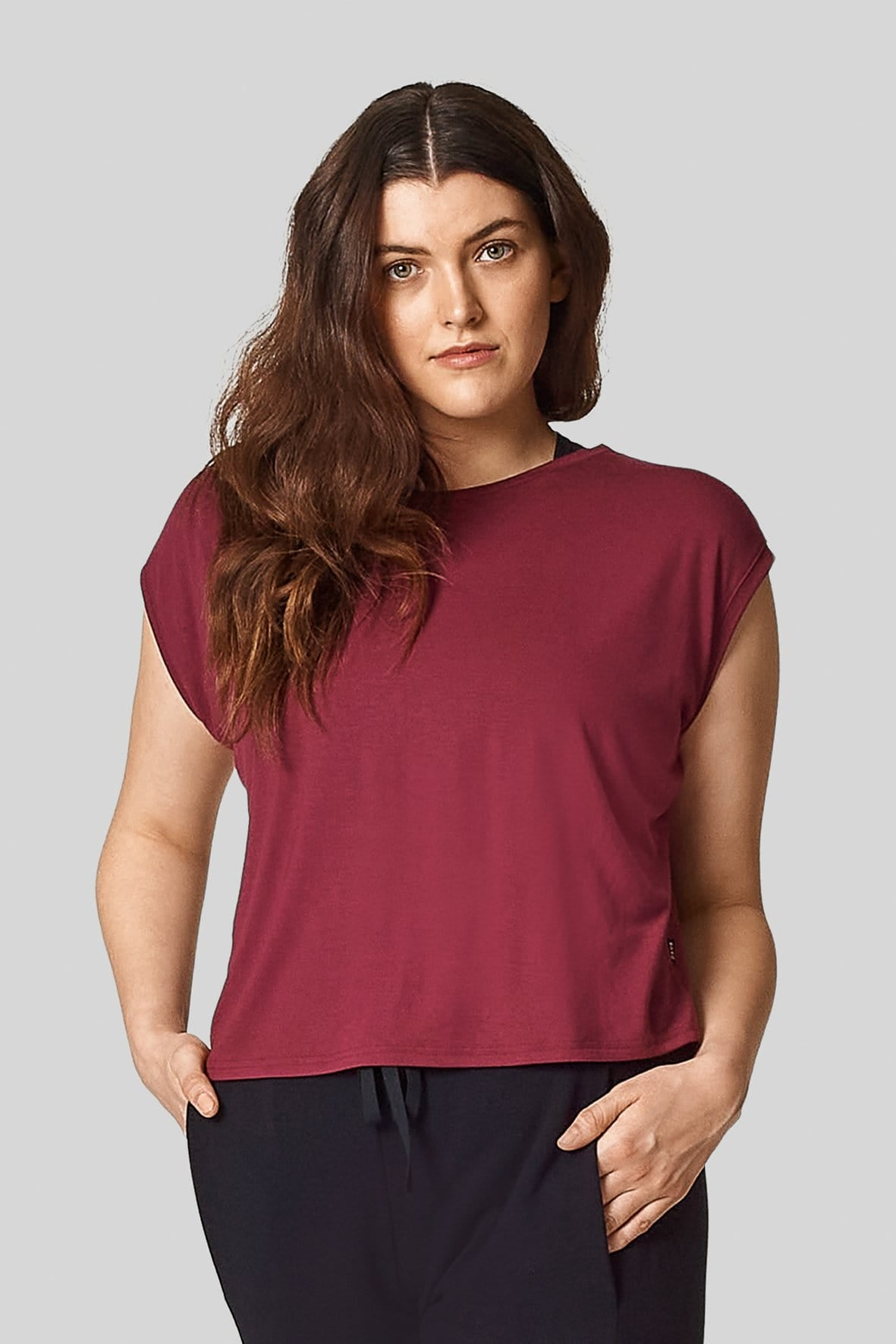 A brunette wears a wine coloured, red tee with a boxy cut.