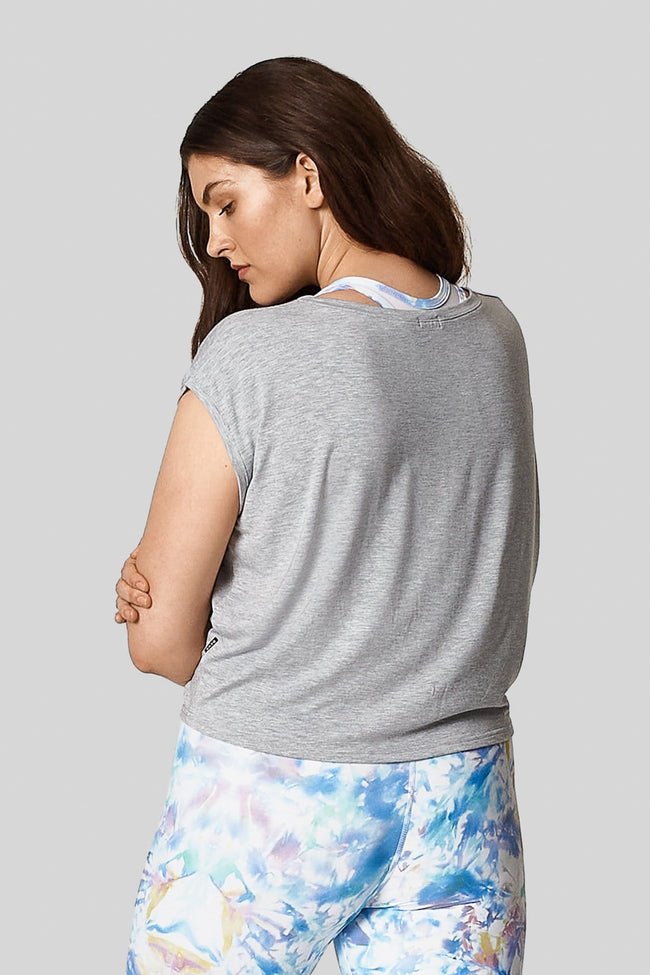 The back view of a brown haired woman wearing a heather grey box tee with printed blue bike shorts.